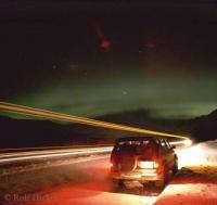The Illumination of the Vehicles vie with the Subtle Beauty of the Northern Lights over Alaska .