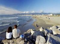 A honeymoon couple sitting on the beach of Viareggio in the Tuscany, Italy