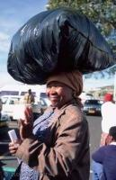 Stock photo of load balancing woman at a market place in South Africa