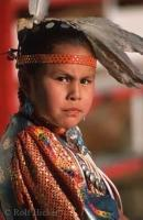 A First Nations girl dressed in traditional native clothing poses for a picture.