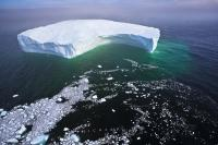 Aerial Photo large free floating iceberg with little ice pieces breaking off and leaving a trail in the deep dark Atlantic Ocean off the Labrador Coast.