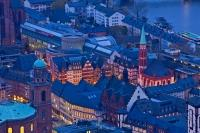 An aerial view of the Roemerberg at dusk, which is the City Hall Square in the City of Frankfurt in Germany shows the architecture and design of an old town perfectly. The buildings are clustered around the main square.