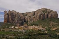 A charming and quaint village known as Aguero in Aragon, Spain sits below the Mallos de Riglos, a large towering red rock crag.
