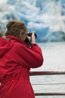 A female tourist photographing a glacier on her vacation in the Juneau area.