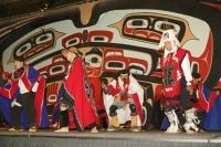 A Colourful Display of American Native Dress and Dance backdropped by the symbols of their People in Juneau Alaska.