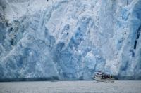 A small tour boat approaches the steep icy wall of Sawyer Glacier south of Juneau in Fords Terror Wilderness Area, Alaska.