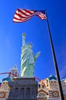 The American flag waving in the wind, framing the Liberty Statue in front of the New York New York Hotel and Casino Resort in Las Vegas, Nevada.