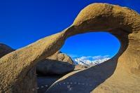 A beautiful scene of the snowcapped Sierra Nevada Mountains framed by Mobius Arch, a rock formation in the Alabama Hills Recreation Area.