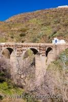 An arched bridge extends across a river next to the town of Valor, Las Alpujarras, which is on the fringes of the Parque Natural de Sierra Nevada, located in the Province of Granada in gorgeous Andalusia, Spain.