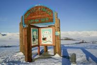 Photo of the wooden arctic circle sign along the Dempster Highway in winter in the Yukon Territory, Canada.
