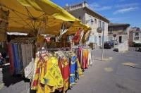 Merchandise of strikingly beautiful colored merchandise is sold at the market outside Les Arenes in Arles, France.