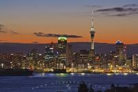 The bright night lights of Auckland sparkle in the after sunset light over the city situated on the North Island of New Zealand.