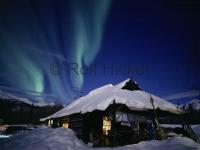 A old trappers cabin in northern Alaska in winter with northern lights above the mountains.