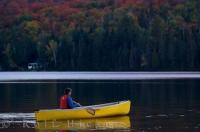 During the sunset hours, a woman spends her time canoeing on the quietness of Rock Lake in Algonquin Provincial Park in Ontario surrounded by Autumn colors.