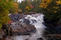 A waterfall along a river that winds through Mont Tremblant Provincial Park in Quebec with the Autumn colors highlighting the scenery.