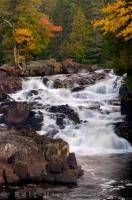 A beautiful scene in Quebec, a waterfall called Chutes Croches tumbles in cascades along the Riviere du Diable surrounded by a typical autumn scene of colourful maples and birch trees.