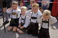 A funny scene of three boys blocking their ears for the gun salute during the Maibaum Festival in Putzbrunn, Germany.