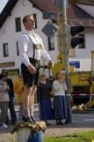 While dressed in traditional Bavarian Lederhosen this man co-ordinated the raising of the Maubaum in Putzbrunn, Germany.