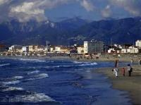 The town of Viareggio with high mountains in the background and the town beach with people in the foreground, Toskany, Italy