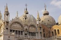 The exterior of the beautiful Basilica di San Marco showing the ornate arches and two of the five domes in Venice, Italy.