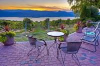 A beautiful sunset adorns the evening sky above Okanagan Lake and a patio setting at a vineyard in Naramata in the Okanagan-Similkameen region of British Columbia, Canada.