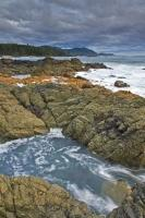 White foamy waves and a rocky coastline are seen along the beautiful scenic West Coast at Cape Palmerston on Northern Vancouver Island. Beautiful blue waters and cloudy skies add to the scenery of Cape Palmerston.