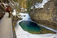 This beautiful scenic canyon is Johnston Canyon in Banff National Park in the Canadian Rocky Mountains. This pool, which is surrounded by ice and snow is a popular tourist attraction in Alberta and many visitors make it a point to stop here.