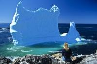 A large beached iceberg reflects shades of blue near the village of Twillingate in Newfoundland, Canada.