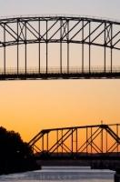 Two bridges, one being the International Bridge, can be seen silhouetted against the sunset over Sault Ste Marie in Ontario Canada. This view was taken from the Soo Locks, which allows ships to pass from Lake Superior to the Lower Great Lakes.