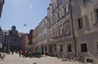 In Bruneck, Italy pedestrians stroll the intimate town lane amongst the businesses and shops.