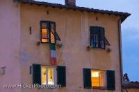 A building surrounding the Old Roman Amphitheatre in the Piazza Anfiteatro at dusk in the city of Lucca, Tuscany Italy. Many buildings in this similar style line the outside of the Piazza, which used to be a Roman Amphitheatre dating from 180 BC.