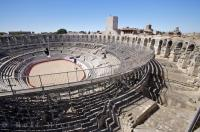The Les Arenes which dominates old Arles, France is a historic bullfighting arena and the popular spectator sport of bullfighting is stilled hosted yearly at the arena.