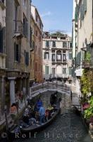 This busy side canal in Venice, Italy, has many people who are doing many things in a very narrow space as gondolas pick up and drop off passengers near the Italian bridges.