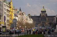 In front of the historic buildings, one being the National Museum, the street is very busy as cars and people fill the area of downtown Prague in the Czech Republic to visit Wenceslas Square.