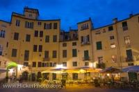 A quaint collection of cafes and restaurants line the outside of the old Roman Amphitheatre in the Piazzo Anfiteatro at dusk. The Piazza, which was originally built in 180 BC is one of the most famous sites in the city of Lucca in the Tuscany, Italy.