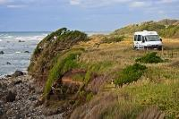 A campervan parked along a grassy road on Cape Egmont, is awarded with stupendous views over the Taranaki Bight on the North Island of New Zealand.