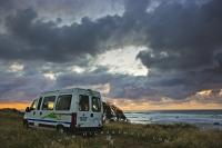 A brooding evening sky looms over a campervan at sunset. Camping along the Taranaki coastline at Cape Egmont is a fabulous experience with the waves crashing ashore just below the cliffs.