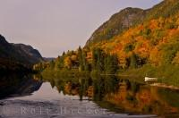 A picture of typical Canadian landscape during the autumn season in Quebec. Colours of fall cloak the mountain sides and reflect on the still waters.