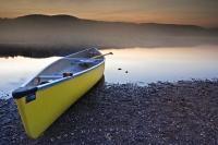 A canoe sits ready to be pushed onto the water on the shores of Lake Monroe as the fog settles over the water at sunset. This picure was taken in Parc national du Mont Tremblant, which is a Provincial Park in Laurentides, Quebec.