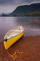 A lone yellow canoe sits on the shore of Lac Monroe in Parc national du Mont Tremblant in the Laurentides region of Quebec on a calm fall evening.