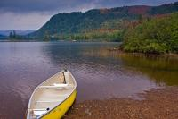 A yellow canoe on the shoreline of Lac Monroe is used as a foreground for this nature fall landscape photograph at Mont Tremblant in Quebec, Canada.