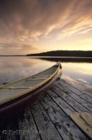 A dramatic sky reflects the sunset on Tuckamore Lake and a Canoe in Main Brook, Newfoundland, Canada.