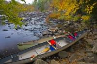 A couple of canoes hauled out on the bank of the Oxtongue River near the Ragged Falls in the Oxtongue River-Ragged Falls Provincial Park in Ontario.