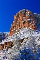 A picture showing the beautiful contrast of white snow and red rock against a vivid blue sky in the Oak Creek Canyon during the winter months in Arizona, USA.