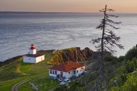 The sunset glistens off the cliffs of Cape d'Or in Nova Scotia, Canada where the Cape d'Or lighthouse, a restaurant and a place for accommodations is located.