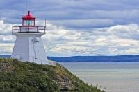 High on a cliff in Albert, New Brunswick, stands the Cape Enrage Lighthouse with its bright red roof and light which aids the water vessels.