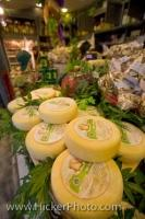 A variety of cheese displayed at a market stall at the Mercato Centrale in Florence, Italy along with shelves of other tempting delicacies.