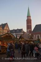 Bundled in their winter clothing, people roam between the stalls at the Christmas Markets in the Romerplatz in Frankfurt, Hessen in Germany, Europe.