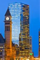 The shiny glass facade of a modern office building contrasts against the illuminated clock face and tower of the Old City Hall at twilight in downtown Toronto, Ontario, Canada.