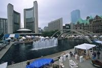 The fountain outside City Hall in Toronto, Ontario is encompassed by many tables and tents that are part of the flea market.